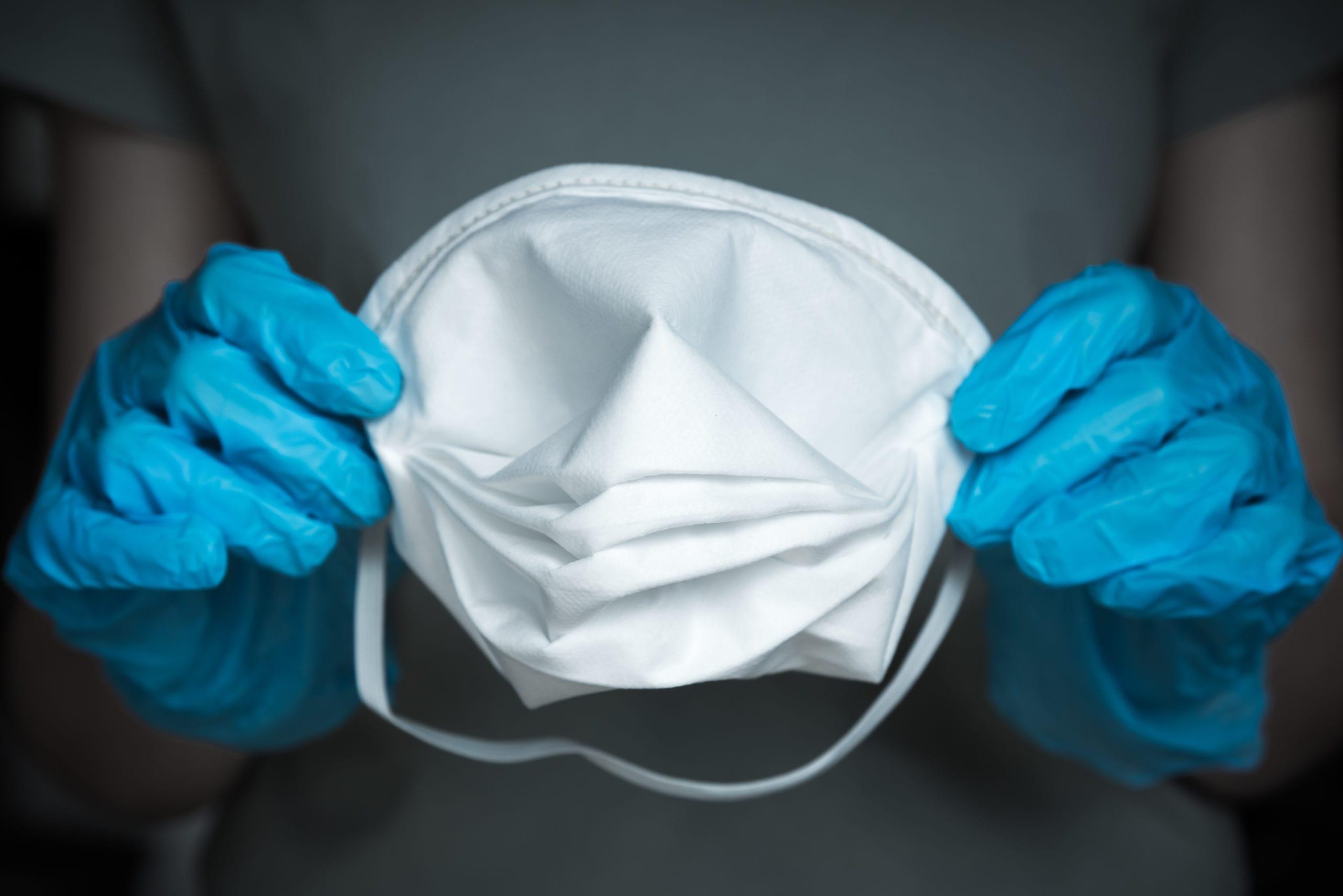 Close-up of gloved hands holding N95 medical face mask
